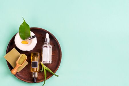Natural cosmetics, oils for skincare and natural soap with leaves and aloe vera in a wooden plate on a blue background Banco de Imagens