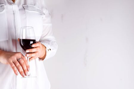 The woman holds glass with red wine on gray background with copy space