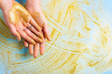 Golden glittering palms. Fashion inspired by golden metallic trend. Copy space Stock Photo