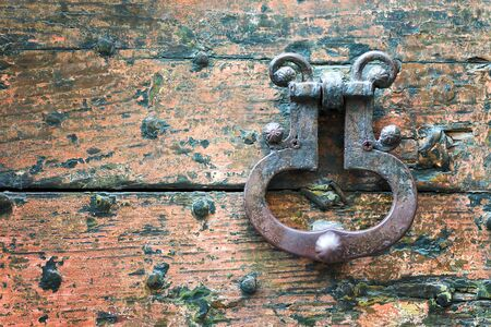 Old metal door handle knocker on a rough wooden background Stockfoto