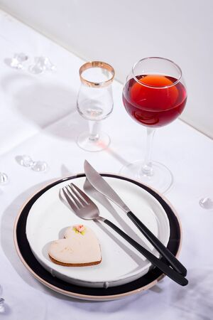 Tableware and decorations for serving a festive table. Plates, red wine glass and cutlery with heart cookie on white textile background.