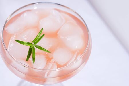 Pink cocktail with rosemary and ice on a white tablecloth on the table Stockfoto