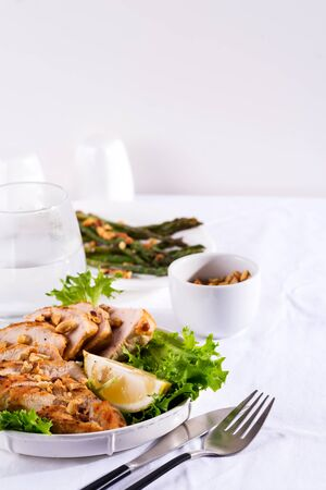 Grilled chicken breast with fresh frize salad, peanuts and lemon on a plate on stone background