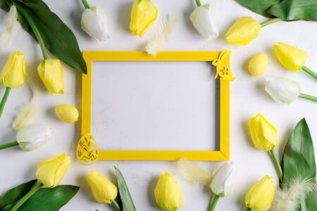 Photo frame with spring tulips with easter bunny on marble background with sample text
