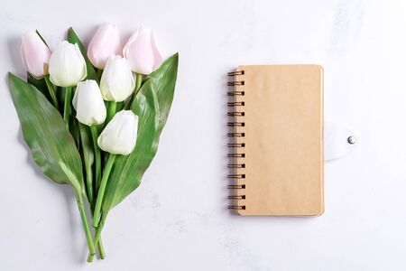 Pastel Tulips with notebook on white marble background, copy space