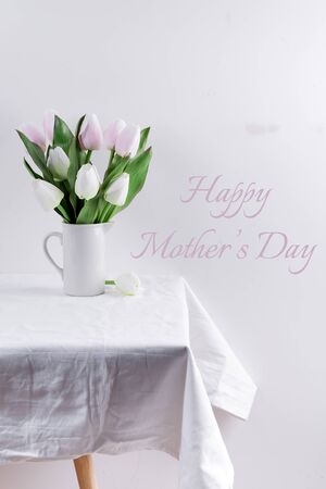 Bunch ofwhite and pink tulips in a white vase on white table with Mothers day lettering