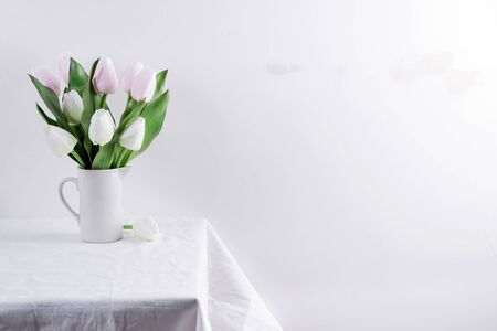 Bunch ofwhite and pink tulips in a white vase on white table