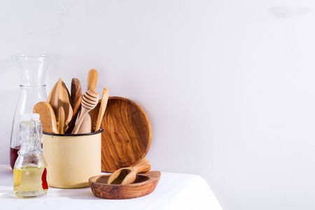 Wooden set of kitchenware in iron cup with wooden plates on white textile table. Cooking appliances. Zero waste