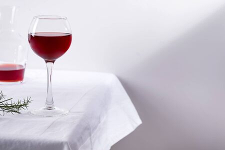 red wine in a wineglass with shadows isolated on white textile background