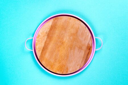 Blank round wooden board in a pink pan on a bright blue background. Flat lay.