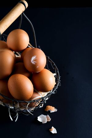 Fresh farm natural organic chicken eggs in basket on a black background with copy space. Happy Easter concept.