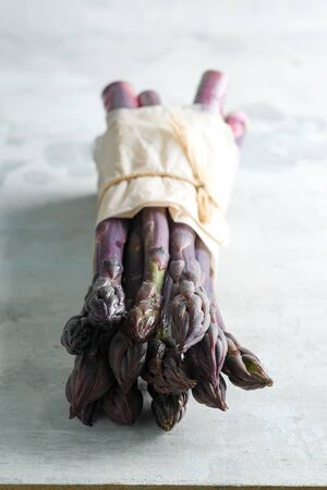 Vertical standing home grown raw organic purple asparagus bunch for cooking healthy vegetarian dieting food against stone background, copy space. Vegan concept.