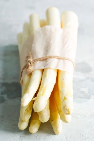 Vegan concept. Organic food. Healthy food cooking concept. Home grown fresh natural organic white asparagus bunch in a paper vertical standing, for cooking vegetarian healthy food against stone background, copy space.