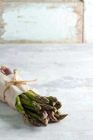 Vegan concept. Organic food. Healthy food cooking concept. Freshly picked vertical standing raw organic green asparagus bunch for cooking healthy vegetarian dieting food against stone background, copy space. Vegan concept.