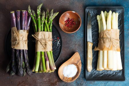 Home grown raw organic purple, green and white sparagus spears, ready for cooking with spaces, healthy vegetarian dieting food on a stone background, copy space. Vegan concept. Reklamní fotografie