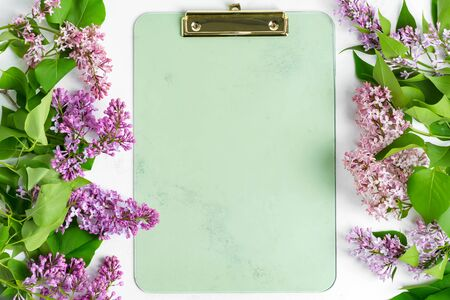 Postard from frame of fresh lilac flowers and clipboard for paper on a light grey marble background. Top view.
