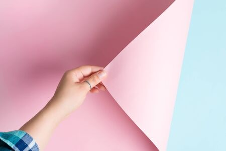 Woman hand is turning pink paper sheet on a blue background with soft shadows.