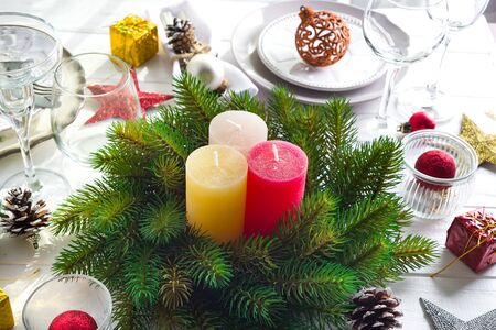 Festive decoration on Christmas table setting with candles, lantern, tableware and wine glasses on white wooden background , copy space