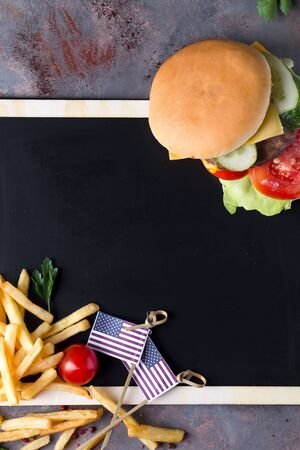 Tasty grilled homemade burger cooking with beef, tomato, cheese, cucumber and lettuce on a chalk board with fries and the US flag