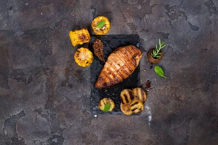 Marinated grilled healthy chicken cooked on a summer BBQ and served with fresh herbs, potatoes and corn on slate plate on the stone background