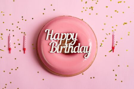 Holiday composition from homemade freshly prepared glazed souffle from natural ripe strawberry, text Happy Birthday above, candles and stars decoration on a pink background, copy space.