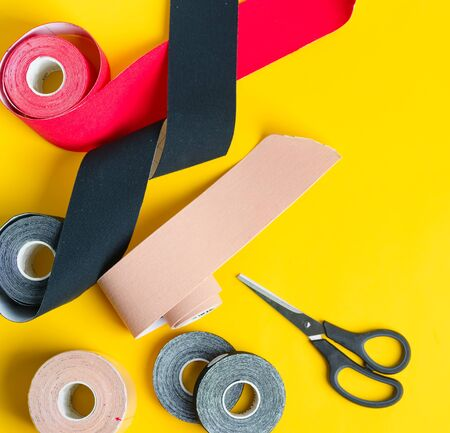 Set for kinesiology taping treatment from special physio tapes rolling of different colors and scissors for cutting on a yellow background, copy space. Top view. Kinesio treatment concept.