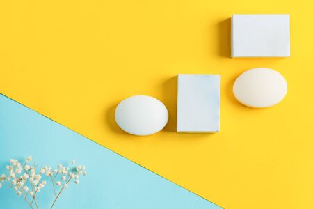 Natural cosmetic skin product handmade soap bar with mockup paper label and without on a pastel duotone yellow blue background. Mock-up for your design and creativity.