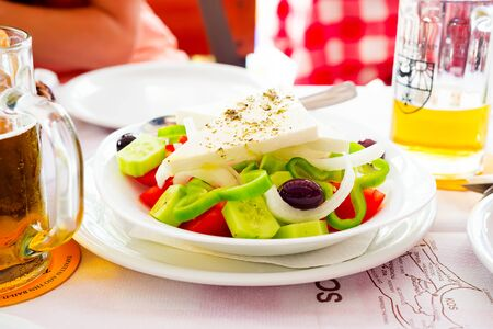 Appetizer for dinner. Plate with Greek salad and beer on a cafe table