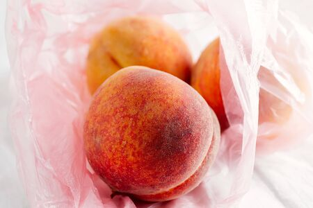 Close-up view plastic bag with natural freshly picked organic peach fruits on a textile background. Standard-Bild - 150231525