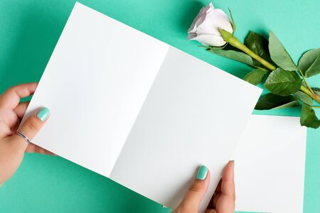 Creative festive card from female's hands holding blank mock up paper sheet for writing letter or message above pastel turquoise background with rose flower, copy space. Top view.
