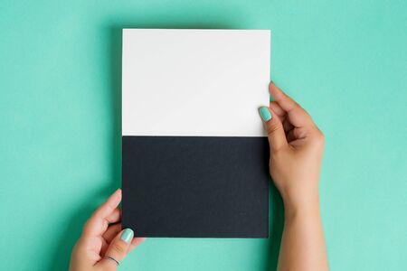 Woman's hands are holding blank mock-up duotone white and black paper sheet for writing text or message above pastel turquoise background, copy space. Top view. Standard-Bild - 150231046