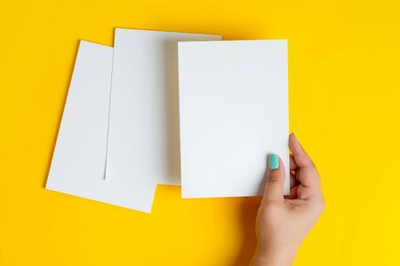 Womans hands are holding empty mock-up brochure for writing letter above yellow background