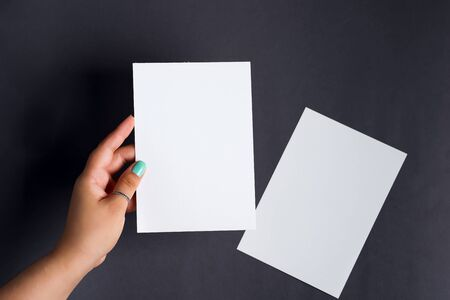 Womans hands are holding empty mock-up brochure for writing letter above black background Standard-Bild