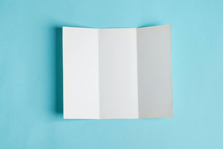 Minimal trifold brochure template above blue background with shadows