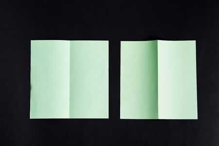 Minimal Folded bifold business green card mockup for writing letter or message above black background with shadows, copy space. Top view. Standard-Bild