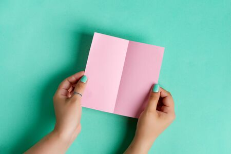 Creative festive card from female's hands holding blank mock up brochure for writing letter or message above pastel turquoise background , copy space. Top view. Standard-Bild