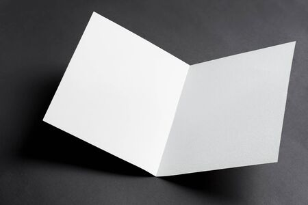 Minimal Folded bifold business white card mockup for writing letter or message above black background with shadows, copy space. Top view.