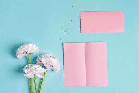 Folded bifold business pink card mockup with beautiful rose flower on blue