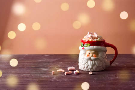 Christmas santa cup of hot chocolate with marshmallow on wooden table. Standard-Bild