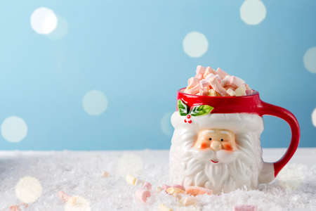 Christmas santa cup of hot chocolate with marshmallow on blue