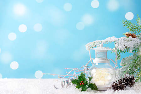Christmas lantern on snow with fir branch and winter decoration on blue