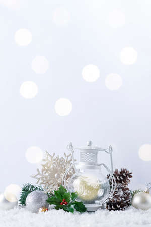 Christmas lantern on snow with fir branch and winter decoration on white