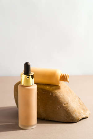 Facial foundation glass bottle cream. Closed container of liquid tone. Beauty and cosmetology branding concept Standard-Bild