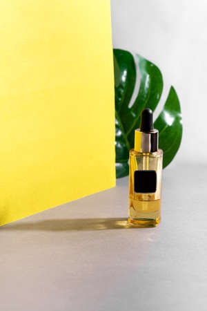 Product is a serum or oil with vitamins for the care of female skin on grey yellow background.
