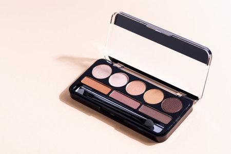 Eyeshadow palette on beige background, eye shadows cosmetics product . Fashion blog design.