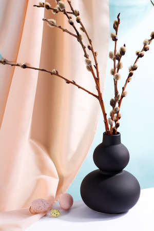 Happy Easter eggs and branches seals in a vase with drapery fabric