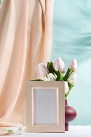 vase with bouquet of beautiful tulips and mockup frame on color background