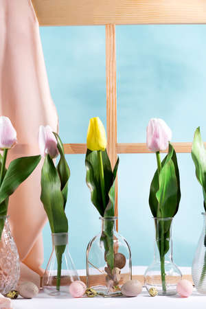 Beautiful tulips in glass vases with easter eggs. Spring flowers for home interior near a window. Decoration for spring.