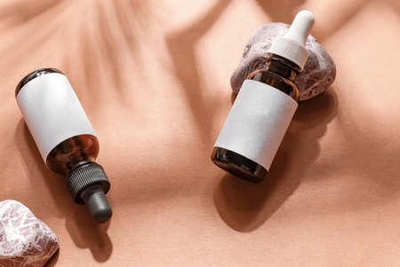 Close-up mockup serum essence in glass bottle on papaya background. Isolated skincare oil Standard-Bild