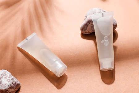 Close-up mockup tubes on papaya background. Isolated skincare oil